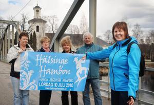 Projektledare Helena Näslund presenterar årets Hälsingehambo på gamla bron i Segersta. Skylten hålls upp av Ingela Berglund, Lena Andersson, Irene Frank och Olle Andersson.