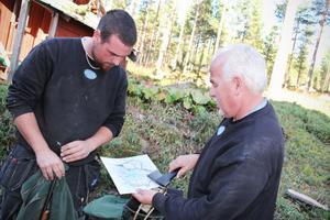 Håkan Nordlund pekar på kartan ut vilket pass han kommer att sitta på när jaktlaget sätter igång på torsdag. Sonen Andreas Söderkvist sitter i närheten.