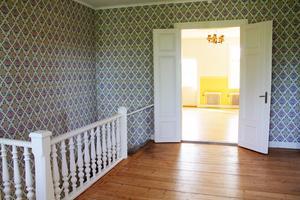 En trappa upp finns denna hall med utgång till den stora balkongen ovanför entrén. Även det stora rummet som skymtar i bakgrunden har en balkong.