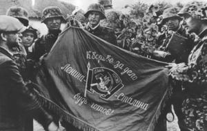 Det första krigsbytet från östfronten, en rysk regementsfana. Tyska soldater beskådar den erövrade fanan, vars text lyder: