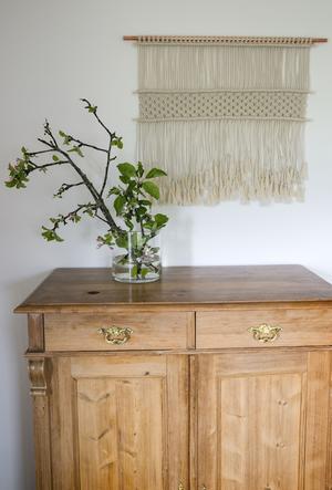 Det enkla är oftast finast, tycker Christel. En naturfärgad makramébonad på väggen och  en äppelkvist på en skänk i trä är ett mjukt blickfång i vardagsrummet.