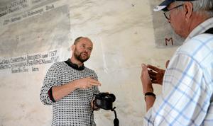 Återskapar. Konservator Gábor Pásztor jobbar med de över 200 år gamla väggmålniningarna i Castorinska kapellet. Viss hjälp kan en kamera med infrarött filter ge, förklarar han för kyrkorådets ordförande Kari Paavonen.