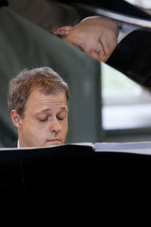 Sundsvallssonen Lars Jönsson där han vanligen sitter, vid flygeln. Musicerandet fyller både arbetsliv och fritid, något som gjort hans åttarige son Nikolai aningen avskräckt.