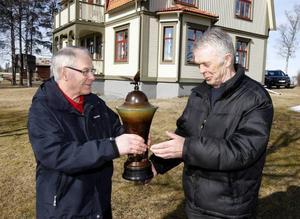 Här sker det högtidliga överlämnandet av den stora pokalen. Bertil Carlsson, till vänster, tycker att det känns bra att Oldens byalag genom Fritz Ragnarsson, får tillbaka sitt vandringspris som funnits på Frösön i 53 år.