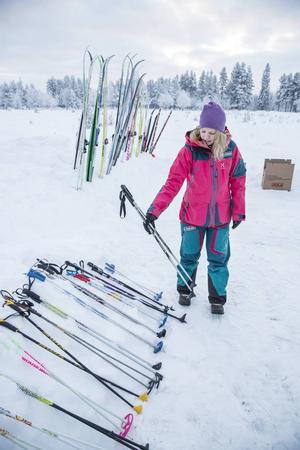 Anne Lundberg sorterar upp skidutrustningen i en snödriva intill skidspåret.
