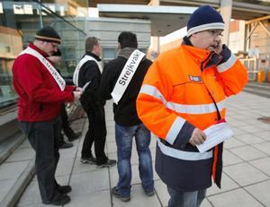Martin Nyman, ordförande för Pappers i Iggesund pratar i telefon, samtidigt som strejkvakterna utanför Iggesunds bruk förbereder sitt skift.