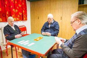 Hans Bergdahl, Rolf Lindberg och Evald Gotthardsson spelar en giv. Under måndagsbridgen var Folkare bridgeklubbs lokal välbesökt.