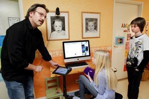 Framför Macen. Patrik Holmström och hans familj på Önsta har skapat ett framgångsrikt och snyggt dataspel på familjens dator. Barnen Ida, 9, och Adam, 12, har varit med och designat spelets banor.Foto: Kenneth Hudd