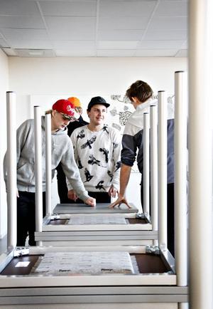 Rasmus Blom och Erik Karlsson känner på möblerna, som eleverna själva varit med och valt ut, i ett av de nya klassrummen.