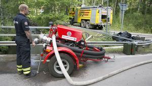Brandman Kenneth Söderström fyller tanken på brandbilen som är utrustad med vattenkanon.