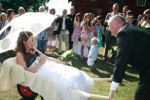 Mikael Halldén kör sin äkta maka Maria Nevelius i skottkärra fram till bröllopsfesten.