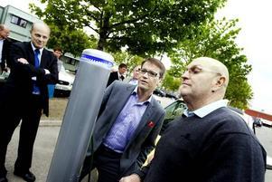 FRÅGANDE MINISTER: Hur laddar man den här bilen då? frågar socialminister Göran Hägglund. Anders Wahlund visar hur man kopplar in och sedan tankar bilens batteri, nu kan man köra 18 mil. Gävle Energis vd Per Laurell inspekterar testet.