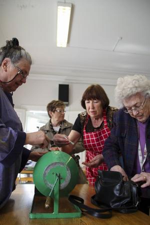 Inger Rehn snurrar på tombolan medan Nora Strid och Märta Moritz ivrigt köper lotter.