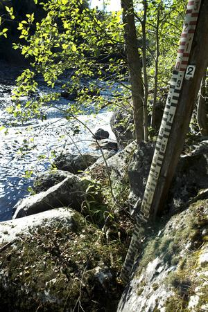 Måttstocken visar hur högt upp vattnet forsade förbi innan regleringen. Där det svarta tar slut var den normala nivån.
