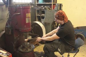 Marcus Brink bearbetar knivbladet med lufthammare