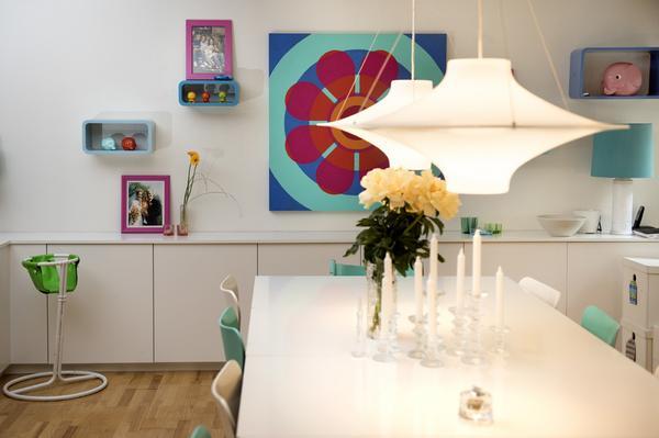 Vitt och färgklickar. Runt matplatsen finns Sjuan-stolar och över bordet hänger två taklampor Lokki av Yki Nummi från 1960-talet. Konstverket i bakgrunden är en kopia av Jim Isermann, som Jonas har målat till Helén.