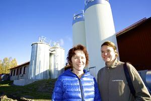 Sylvia Falkeström och Erika Olsson pekar ut riktningen för Oppigårds bryggeri. Bakom dem pågår bygget av det nya bryggeriet.