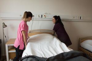 Personalstyrkan är positiv och välkomnande. Undersköterskorna Lina Svensson och Sofia Wallin bäddar en säng och förbereder de sista rummen för inflyttning.