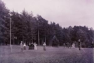 Med fotsida klänningar för damerna och kostymer för herrarna spelades den första tennisen i Hedemora. Bilden är från 1896 och visar Hedemoras första tennisbana, som anlades på Stadsberget.