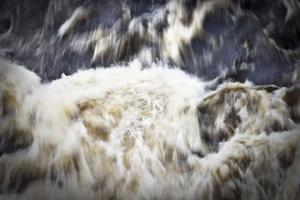 Vattnet bildar kreationer av vita vågor som lägger sig vackert över den mörka vattenytan.