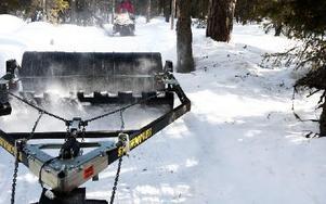 Med Snowmovern på släp plattar de till snön och som vid töväder när det blir gropar lappar de med granris, skottar på mer snö och åker igen. Foto: Johnny Fredborg