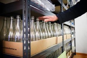 Flaskor i rader. 50 kilo äpplen, som är minimum för kunden, ger ungefär 25 liter, alltså 33 flaskor, must.