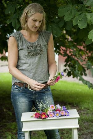 Steg för steg:Ellinor Anger börjar med att rensa stjälkarna, alla blommor håller sig bättre om det inte är blad i vattnet (för fler tips om hållbarhet, se faktaruta). Sedan lägger hon två aster-stjälkar i kors.