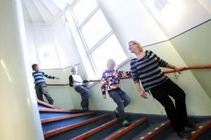 På väg mot mellanmål i källarvåningen på Småskolan. Regina Nyström, fritidspedagog, går ner med några av barnen i ettan.