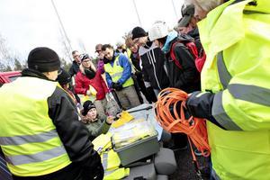 Annelie Ström skriver upp namnen på deltagarna och delar ut gula västar inför sökningen i skogen.