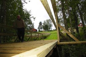 Åke Bogg vid nya träbron som är 2,5 meter bredd och försedd med rejäla räcken. Foto:Hans Olander