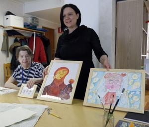 Märit Hansson och Laila Persson visar upp några av tavlorna som kommer att säljas på temadagen.