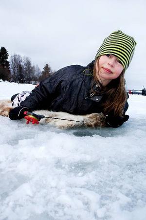 """Nioåriga Sanna Lindqvist har en klar pimpelfisketaktik. """"En granne har lärt mig att rycka tre gånger, och därefter hålla spöt stilla en stund. Sen ska man låta linan sjunka till botten och sedan dra upp igen"""", säger hon."""