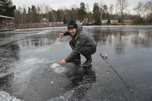 Hugger genom isen med yxa och metar gör fiskeentreprenören Erik Östlund på Kungsholmen utanför Bollnäs.
