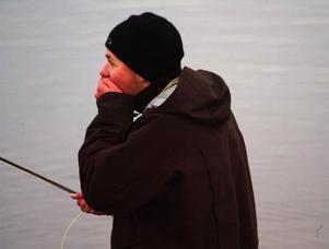 Olle Björk värmer sina fingrar, för det var kallt att flugfiska under gårdagen.