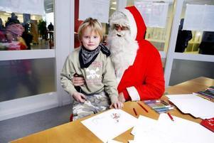 MYSIG PRATSTUND. Rasmus Lasander fick en mysig pratstund i Gästriketomtens knä. Han är sju år och valde att porträttera tomten själv på sin teckning som han sedan gav bort.