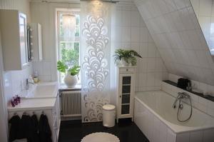 Stort badrum med inkaklat badkar och fint ljusinsläpp.