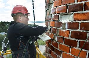Korgen svajar i blåsten när muraren David Berge renoverar skorstenen.