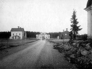 Stationsvägen år 1900. Samtliga byggnader på bilden byggdes 1899. På Brukshotellet, till vänster, åt ogifta tjänstemän. Hotellet var också öppet för andra gäster och representation. Byggnaden revs år 1978. Järnvägstrafiken Kolbäck-Ramnäs startade år 1899. Järnvägsstationen, i mitten, är i dag privatbostad. Huset till höger är Arbetarnas Handelsbolags AB:s affär. Bolaget startade sin verksamhet vid Blåsbacken, Nybygget, men flyttades sedan till lokalen på Stationsvägen. År 1925 övergick Surahammars Arbetares Handels AB till konsumtionsföreningen. Huset är i dag rivet, och där ligger nu bostadshus. Byggnaden som skymtar till höger är ett gravkapell, som var beläget där under några år. Bakom granen ligger i dag Vandrarhemmet, som tidigare var sjukstuga.