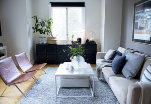 Vardagsrummets soffa och bord ramas in av en stor matta.