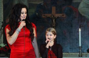 Nioåriga Kristin Nyegård ur församlingens flickkör sjöng Låt mig få tända ett ljus tillsammans med Nina Söderquist.