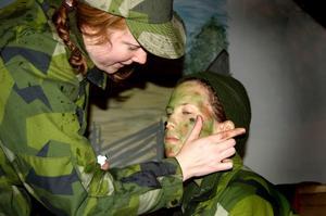 Malin Ahlm-Marklund hjälper Elisabeth Mård med kamouflagesminkningen som de yngre tjejerna senare ska få prova på.