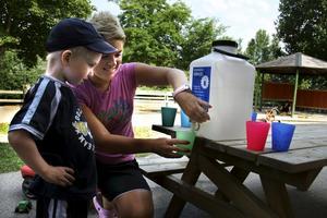 Viktigt vatten. Isak Thornberg, som vanligtvis går på Dungens förskola, tar en vattenpaus i värmen på sommarförskolan tillsammans med förskolläraren Ullis Witt.