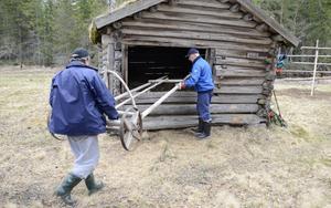 Slåtterkärran ska in under tak. Någon har nämligen lyft ut kärran och så ska det inte vara. Det fixar Kjell Hansson och Leif Ljungkvist.
