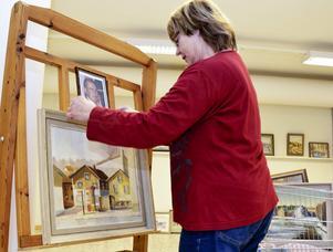 Hedersutställare. Nyligen avlidne Gunnar Olofsson är hedersutställare. Här sätter Lillemor Israelsson upp hans porträtt vid en av de tavlor han bidragit med till utställningen.