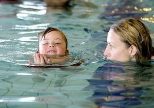 Emelie Eng njuter av att gå i simskola och mamma Marie finns till hands strax intill.
