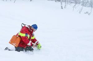 Här har det gått en lavin och fjällräddare Bergström letar efter sändare under snön.
