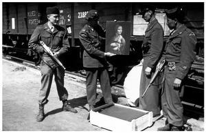 MFAA-officerare med Leonardo da Vincis Dam med Hermelin som 1945 återfanns hemma hos nazisten Hans Frank utanför München. Målningen hade plundrats från Czartoryskimuseet i Krakow. Foto: Okänd fotograf.