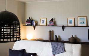 I vardagsrummet har de byggt ett hyllsystem på väggen bakom soffan.