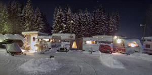I den kalla vinterkvällen lyser det hemtrevligt i den lilla husvagnsbyn nedanför slalombacken i Edsbyn. Här firar husvagnsfolket nyår.