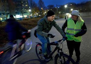 Patric Saverman som cyklade utan utan lyse får  information av NTF:s Rosita Augustsson på Vasatorget i Örebro.